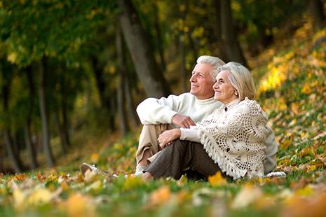 Hombre y mujer mayores sentados en el suelo en el campo mirando al horizonte