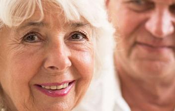 Dos mujeres y un hombre mayor sonriéndose entre sí