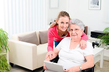 Señora mayor en silla de ruedas y abrazada por el hombro por mujer joven