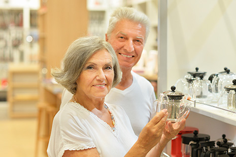 Mujer mayor con una jarra de cristal en las manos junto a un hombre mayor en tienda