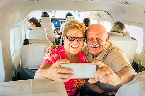 Hombre y mujer mayores dentro de un avión sujetan y miran hacia un teléfono móvil