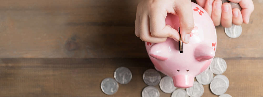 Mano introduciendo monedas en una hucha con forma de cerdo