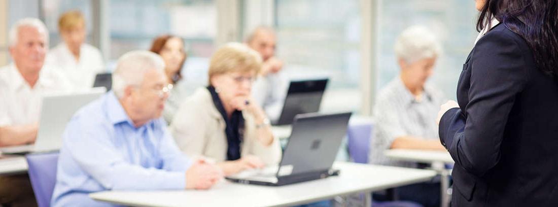 Mujer mayor sujeta tableta junto a joven que señala sobre la pantalla