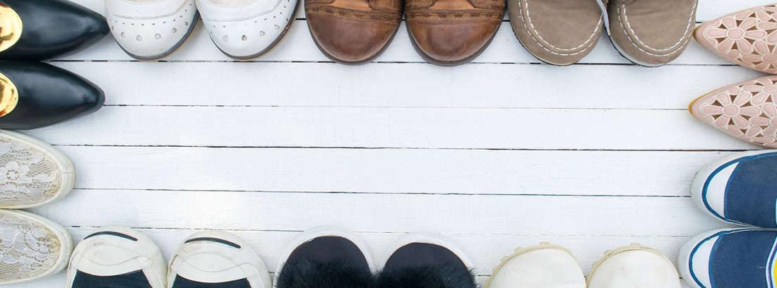 Diferentes filas con calzado variado detrás una vista parcial de pies y piernas