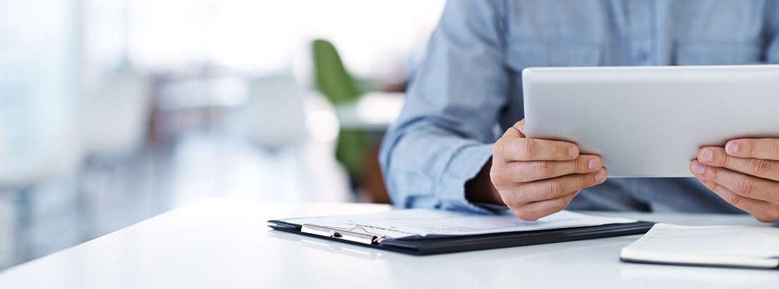 Hombre y mujer maduros, sonrientes y cómodos con una tableta en la mano