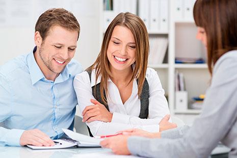 Hombre y mujer jóvenes miran hacia un papel que les muestra otra mujer