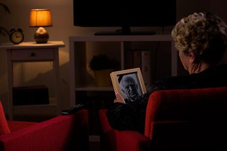 Mujer mayor mira hacia foto de hombre mayor que sostiene en sus manos
