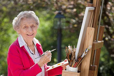 Mujer mayor con pincel y paleta delante de un lienzo