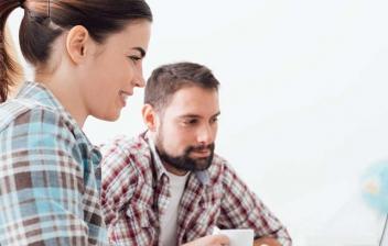 Hombre y mujer jóvenes con papeles y tableta sobre una mesa