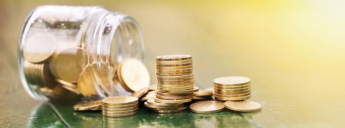 Monedas apiladas y otras caídas junto a calculadora, cuaderno y bolígrafo