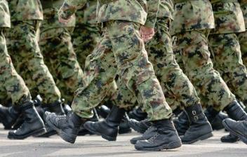 Fila de personas con manos sujetas a la espalda y vestidos con uniforme militar