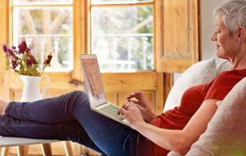 Mujer madura sentada en jardín y con tableta entre las manos