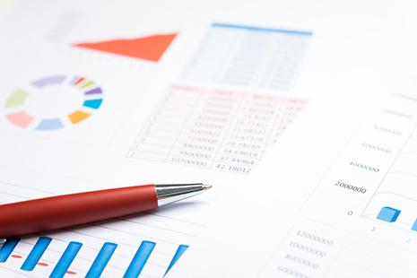 Bolígrafo sobre papel con números y gráficos estadísticos varios