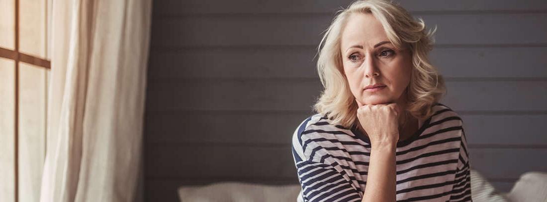 Mujer mayor con mano apoyada sobre la boca y ojos mirando hacia abajo