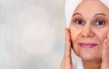Reflejo en espejo de cara de mujer madura echándose crema