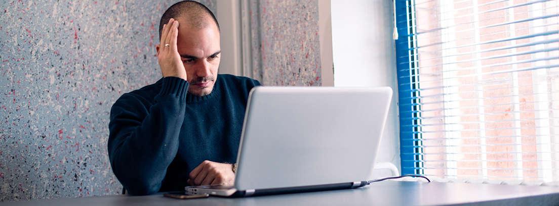 Hombre con gesto preocupado frente a un ordenador