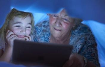 Niña sonriente abraza a mujer mayor también alegre