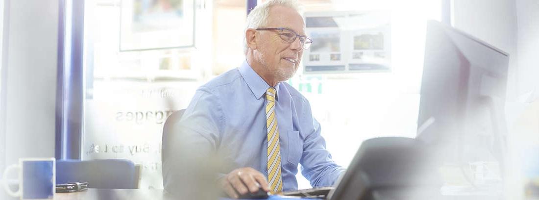señor mayor mirando la pantalla del ordenador portátil, con la mano en la barbilla