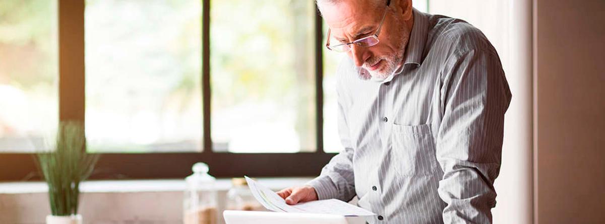 Hombre mayor mirando unos documentos