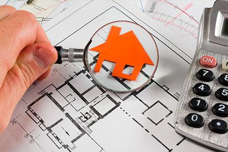 Mano sostiene lupa sobre un plano y silueta de casa en color naranja junto a calculadora