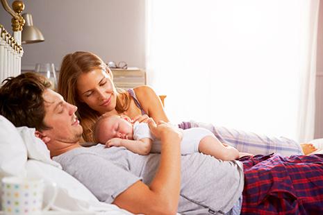 Hombre tumbado con bebé sobre él y mujer junto a ellos