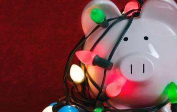 Figura de cerdo con gafas y gorro rojo con borla blanca rodeado de adornos de Navidad