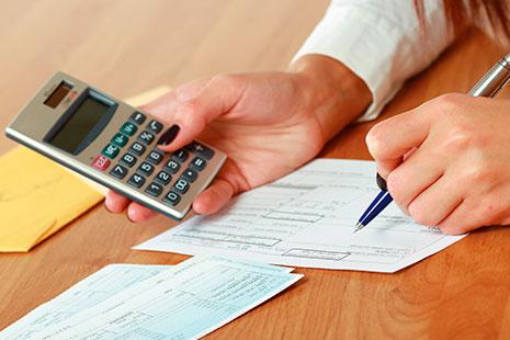 Mano sujeta calculadora y otra bolígrafo sobre papel