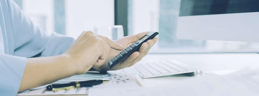 Hombre con mano sobre calculadora y otra sujetando papeles