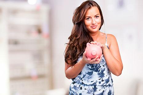 Mujer sonriente sujeta en su mano una hucha con forma de cerdo rosa