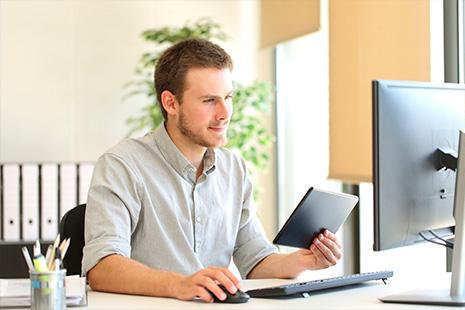 Hombre joven delante pantalla ordenador con tableta en una mano y ratón en otra