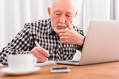 Hombre mayor pensativo sujeta boli sobre papel delante de un ordenador portátil