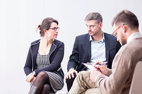 Hombre y mujer se miran serios y frente a ellos otro hombre que apunta sobre un papel