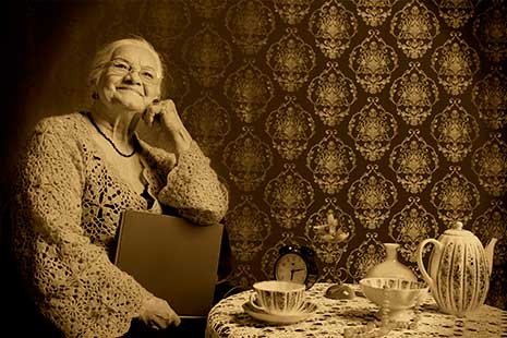Foto en tonos sepia que muestra mujer mayor con gesto sonriente y gafas