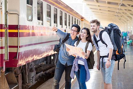Dos hombres jóvenes y una mujer con plano y mochilas junto a un vagón de tren