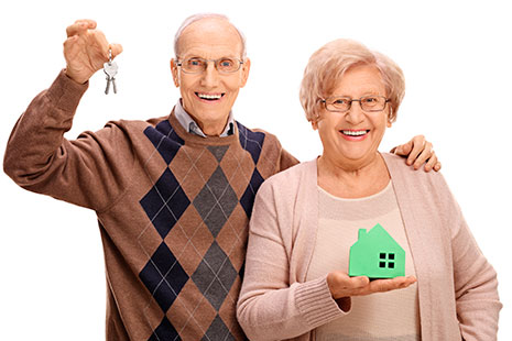 Hombre mayor con llaves junto a él mujer mayor con maqueta casa en la mano