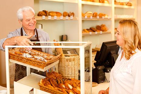Hombre mayor detrás de una vitrina con bollos mira a una mujer sonriente