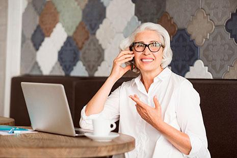 Mujer madura con gafas y pelo blanco delante de ordenador y con teléfono
