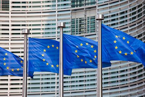Cuatro banderas azules con circulo de estrellas amarillas ondeando