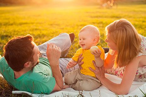 Hombre, bebé y mujer tumbados sobre la hierba