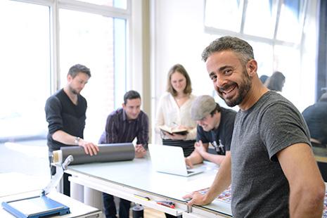 Hombre sonriente apoya mano sobre mesa en la que trabajan hombres y mujeres