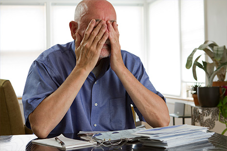 Hombre mayor con manos tapando su cara y sentado en una mesa con papeles