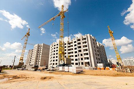 Grúas de obra delante de pisos de viviendas a medio construir.