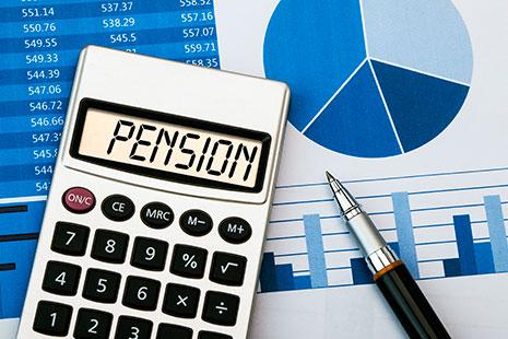 Calculadora junto a boli y gráficos en su pantalla se lee pensión