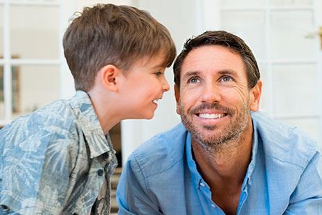 Hombre mirando hacia arriba y niño con boca abierta cerca de su oreja