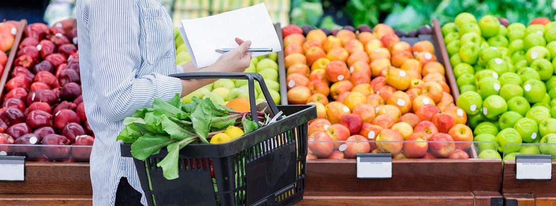 Mujer joven con bolsa de papel entre los brazos llena de frutas y verduras