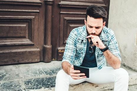 Hombre joven con mano apoyada en la barbilla mira una tableta