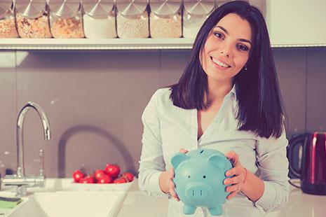 Mujer sostiene una hucha de forma de cerdo azul entre sus manos