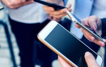 """Una mujer de espaldas con un móvil frente a un ordenador con una web en la que puede leerse """"job search""""."""