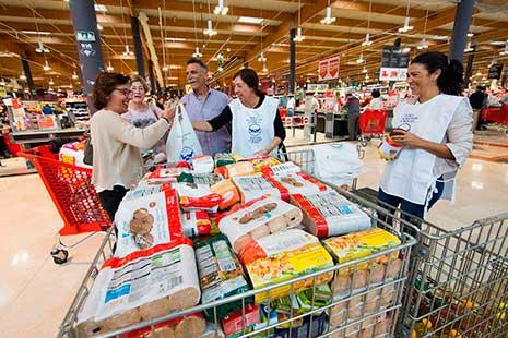 Hombres y mujeres en torno a un contendor con alimentos
