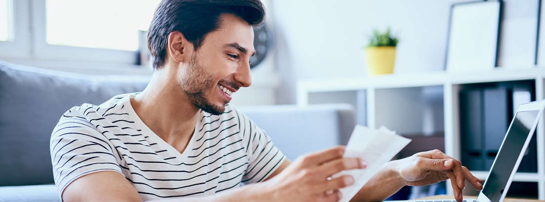 Mujer sonriente con gafas mira papeles y teclea en un ordenador portátil